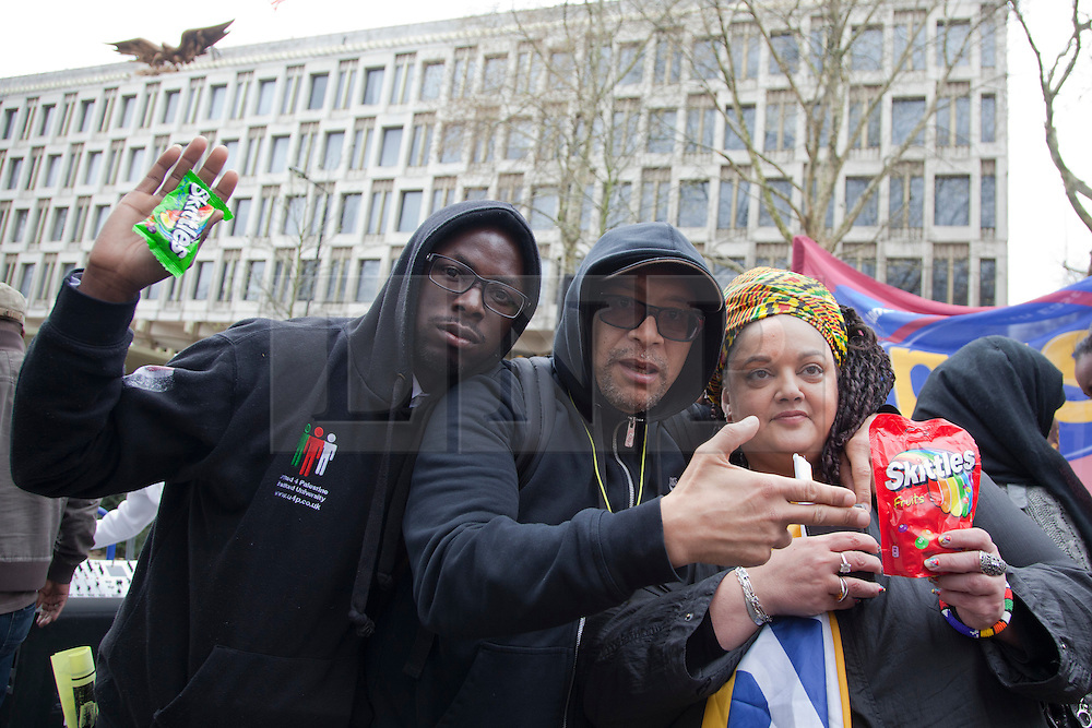 © Licensed to London News Pictures. 31/03/2012. London, England. Lee Jasper (centre) and Zita Holbourne (right) of BARAC hold an empty bag of Skittle sweets as they protested outside the U.S. Embassy in Grosvenor Square, London against the shooting of black  youth Trayvon Martin by George Zimmermann in Sanford, Florida. Trayvon Martin was carrying an empty bag of Skittles when he died. Photo credit: Bettina Strenske/LNP