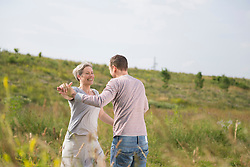 Mature couple enjoying nature on nature in field, smiling