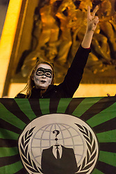 London, November 05 2017. Anti-capitalists gather in Trafalgar Square, London for the annual 'Million Mask March' which happens on November 5th every year, with many of the protesters donning 'V' For Vendetta Guy Fawkes masks. Past marches have turned violent with police horses shot by fireworks and police vehicles burned. PICTURED: A woman with an Anonymous internet activism group's flag makes the 'V' for victory sign . © Paul Davey