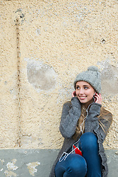 Teenage girl listening to music on mobile phone and leaning against wall, Munich, Bavaria, Germany