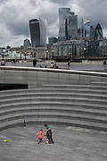 Young boys play football opposite the skyline of the City of London, the capital's financial district, during the UK's Conoriavirus pandemic lockdown, on 7th June 2020, in London, England.