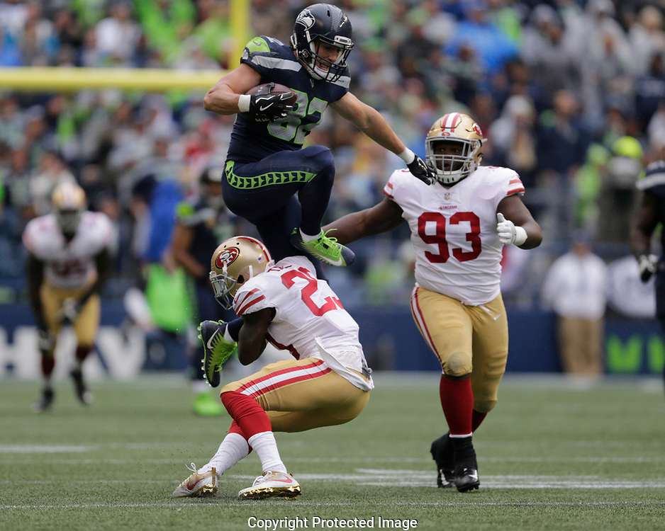 In this second in a series of seven photos, Seattle Seahawks tight end Luke Willson leaps over San Francisco 49ers cornerback Will Redmond, left, as defensive tackle D.J. Jones (93) looks on in the first half of an NFL football game, Sept. 17, 2017, in Seattle. (AP Photo/John Froschauer)