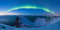 Northern lightw fill night sky from summit of Ryten, Moskenesøy, Lofoten Islands, Norway