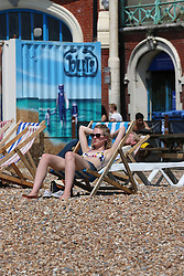 © Licensed to London News Pictures. 13/06/2014. Brighton, UK. A woman sunbathing on Brighton beach. Today, Friday 13th June is expected to be the hottest day of the year so far with temperatures hitting nearly 30C at some locations. Brighton beach is slowly filling up with sunbathers and people wanting to relax by the beach. Photo credit : Hugo Michiels/LNP