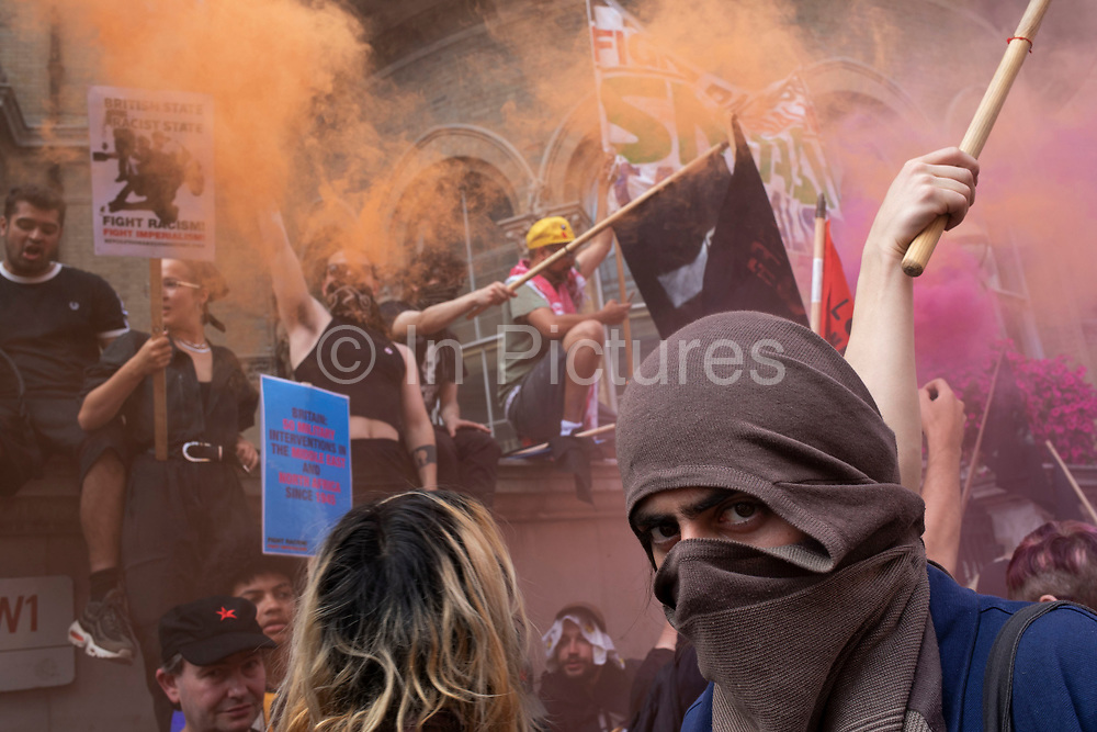 Demonstrators wearing masks gather as smoke flares billow colour to oppose the Free Tommy Robinson demonstration, organised by anti-fascist groups including Stand up to Racism opposed to far right politics on 24th August 2019 in London, United Kingdom. Some 250 Stand Up To Racism and other anti-fascist groups took to the streets today in opposition to supporters of jailed 'Tommy Robinson' real name Stephen Yaxley-Lennon at Oxford Circus, who gathered outside the BBC.
