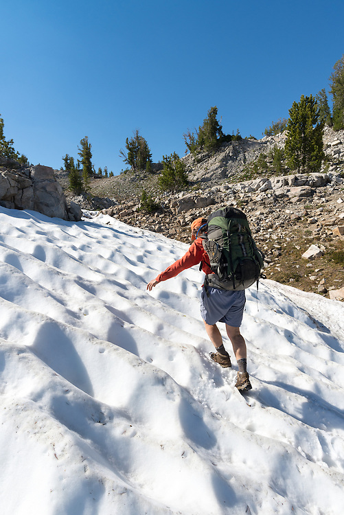 Backpacker hiking up a suncupped snowfield, Wallowa Mountains, Oregon.