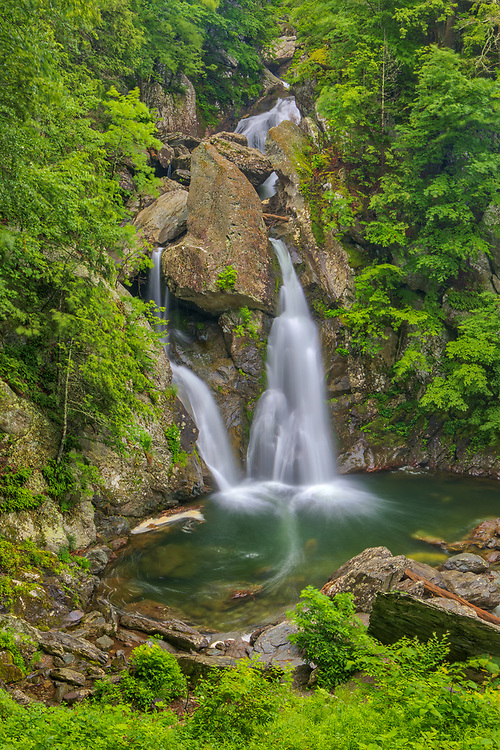 Visiting Bash Bish Falls State Park is always a ton of fun. Bash Bish Falls is one of the most scenic and beautiful waterfalls in New England. So glad to have the falls relatively near by in Berkshires County of Massachusetts, 2 hours and 30 minutes from home to be precise. It's been a while since I came out here photographing waterfalls but last Friday time was right and I traveled to Western Massachusetts to visit my favorite waterfall in the Bay State. Upon arrival, rain was still coming down in a good pace. I grabbed an umbrella and walked the 3/4 mile from the parking area to the falls. The adrenaline level rose with each step I took alongside Bash Bish Brook, the roaring of the falls became apparent and louder as closer I got. Then you arrive at your final destination, looking straight ahead, facing these majestic falls. It's just amazing and I love this scenic waterfall view. Equipped with my Canon 24-70mm lens I got to work capturing this  highest single drop waterfall. Rain and keeping the lens dry was a pain at first, but luckily it stopped raining soon after I started photographing. This made things more pleasant and easier, allowing for further exploration of this Waterfall Photography hotspot and more picture taking.<br /> New England waterfalls photography images are available as museum quality photo, canvas, acrylic, wood or metal prints. Fine art prints may be framed and matted to the individual liking and interior design decoration needs:<br /> <br /> https://juergen-roth.pixels.com/featured/bash-bish-falls-state-park-juergen-roth.html<br /> <br /> Good light and happy photo making!<br /> <br /> My best,<br /> <br /> Juergen<br /> Licensing: http://www.rothgalleries.com<br /> Instagram: https://www.instagram.com/rothgalleries<br /> Twitter: https://twitter.com/naturefineart<br /> Facebook: https://www.facebook.com/naturefineart