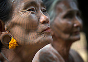 The tattooed women of Burma: Extraordinary photographs show elaborate facial inkings of the tribe whose traditions are dying out<br /> <br /> Their faces covered in elaborate black patterns and, in some cases, totally dark with ink, these smiling villagers are some of Burma's last surviving tattooed women.<br /> <br /> A custom that, according to legend, began when an ancient king tried to make slaves of the women, the inkings were first intended to repel incomers and then became a symbol of beauty.<br /> But with younger people increasingly reluctant to be inked for fear of ridicule and for fear of the heavy fines imposed by the ruling military junta, Burma's tattooing tradition is on borrowed time and could disappear within a generation.<br /> <br /> As a result, few women now have the markings, with the majority of those who do living hidden away in the mountainous Chin, Rakhine and Arakan regions - all of which were closed off to visitors until two years ago.<br /> <br /> Now an estimated 700 tourists travel to the area each year, although few are inclined to attempt the precipitous climb up to the mountain eyries of the Magan, Chin and Muun tribes.<br /> Those who do will be rewarded with a warm welcome - and a glimpse into one of Asia's oldest, and most threatened, cultures.<br /> Most of the tattooed women boast spider's web designs which, as one villager quipped 'attract the men like a spider's web catches insects'.<br /> Others bear full-face tattoos, with every part of their face covered in ink - again, a symbol of beauty. So popular did the look become, one elderly lady, Pa Late from the remote Kanpelet village, revealed that women who chose not to have it 'looked ugly to all the men'.<br /> <br /> The tattoos, which are created using thorn needles and an ink made from a mixture of cow bile, soot, plants and pig fat, are also a sign of bravery - particularly those etched on the neck, which are the most painful of all.<br /> In the past, women who tried to