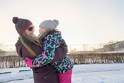Woman embracing daughter on snow field