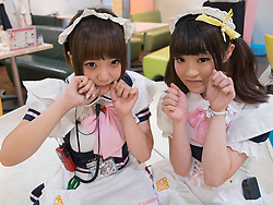 Two young Japanese girls working at Maids' Cafe in Akihabara district of Tokyo Japan