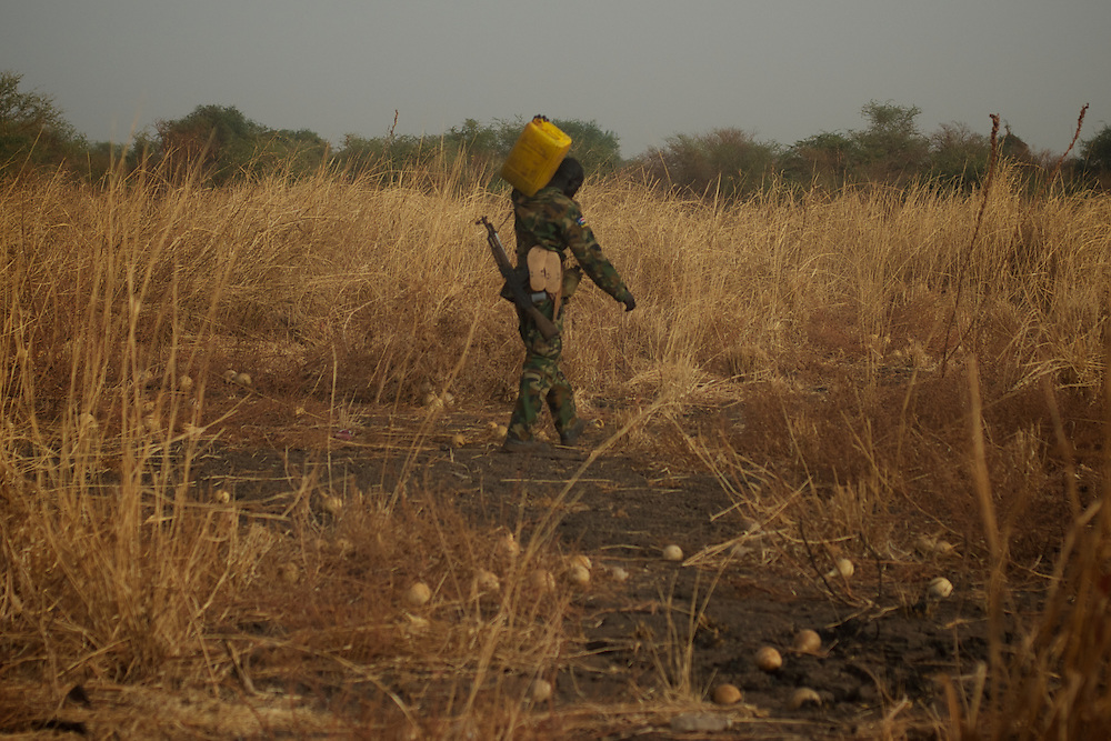 April 24, 2012 - Panakuach, South Sudan: A  SPLA soldier walks by carrying a water canister in the last defensive line outside the village of Panakuach, 70 kilometers north of Bentiu...South Sudan and their northern neighbors, Sudan, have in the past two weeks been involved in heavily clashes over border disputes. Bentiu and neighboring villages have been under constant bombardment by the troops os Karthoum , who established their positions around 10 kilometers into South Sudan's territory. The international community is concerned about the possibility of a full on war between the two countries. (Paulo Nunes dos Santos/Polaris)