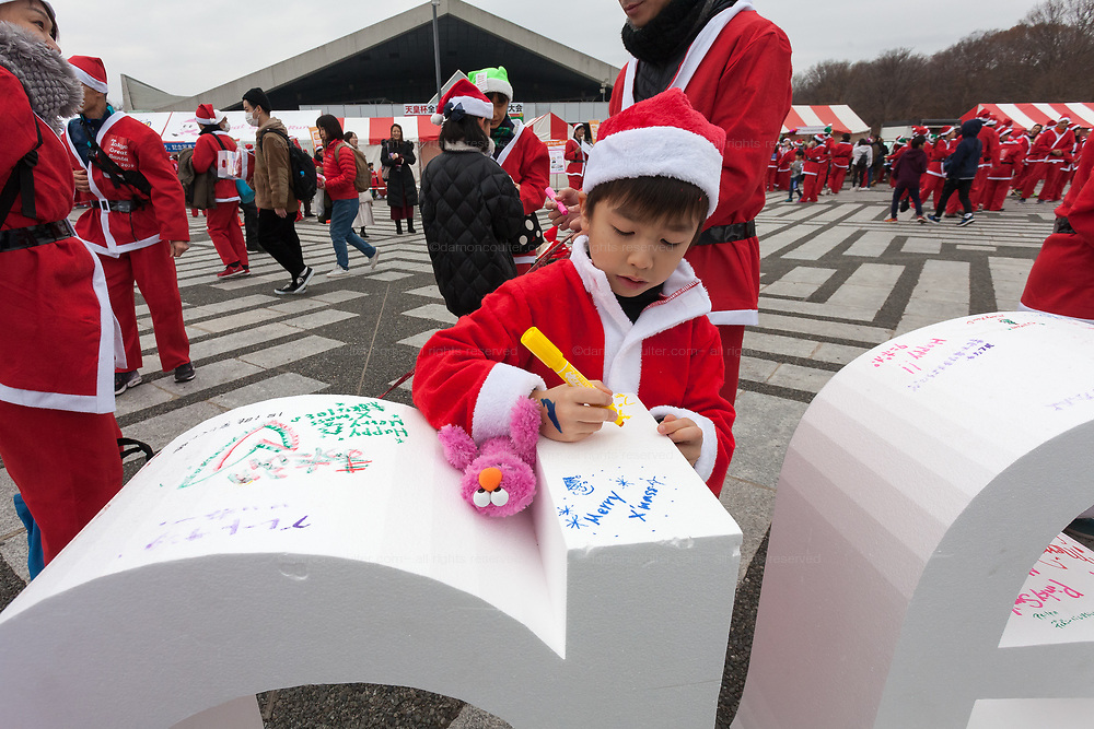 """Participants write Christmas messages on large letters spelling """"Santa"""" before taking part in the Tokyo Great Santa Run in Komazawa-daigaku Olympic Park, Tokyo, Japan. Sunday December 22nd 2019, The great Santa Run was first run in Tokyo in 2018. This years run saw over 3,000 people in Santa costumes run and walk a 4.3 kilometre course to raise money for medical charities in japan and water projects for the Maasai in Kenya."""