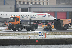 ©Licensed to London News Pictures. 08/02/2021. London UK. Snow ploughs at London City Airport clear the runway of snow and ice after storm Darcey brought snow and freezing weather to much of London and the home counties : Photo credit, Steve Poston/LNP