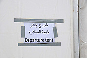 Greece . Idomeni transit camp for refugees travelling from Turkey to Northern Europe,on the border of Greece and Macedonia. Sign in English and Arabic saying 'Departure tent'.