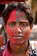 Man with colourful paint powder on his face during the festival of Holi, in Jaipur, Rajasthan, India