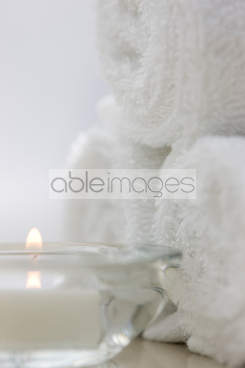 Close up of a burning tea light and rolled up white towels