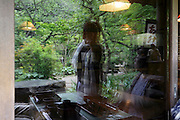 window reflection of two people in a garden Japan