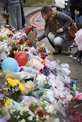 © Licensed to London News Pictures. 13/11/2016. Croydon, UK. A woman places flowers amongst flags, balloons and other tributes to the victims of the Croydon  near Sandilands station. Engineers are working to restore the line at the site where seven people died and 50 were injured when a tram rolled over on Wednesday 9th November. Photo credit: Peter Macdiarmid/LNP