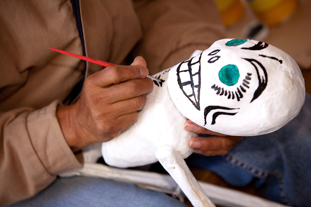 North America, Mexico, Guanajuato State, Guanajuato,  man's hand painting skeleton for Day of the Dead celebration.  The historic city of Guanajuato is a UNESCO World Heritage Site.