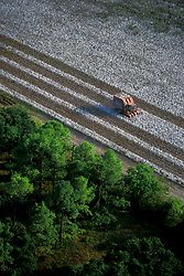 Stock photo of an aerial view of a machine havesting a cotton field