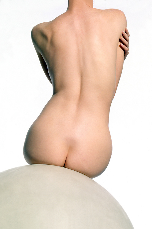Rear view of nude woman sitting on white globe hugging herself