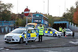 © Licensed to London News Pictures. 27/10/2019. Salford, UK. Police close roads to traffic as they conduct a survey of the scene . A car lies on its side on a pedestrian walkway at the Pendleton Roundabout on Broad Street in Salford . Members of the public pulled a man and a woman from the wreckage after a BMW car crashed through a barrier and landed on a pedestrian walkway below . Their condition is unknown and police , paramedics and fire crews are at the scene . Photo credit: Joel Goodman/LNP