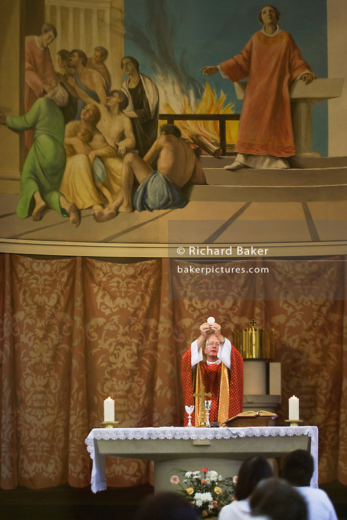 Priest raises wafer during Liturgy of the Eucharist Mass at St. Lawrence's Catholic church in Feltham, London.