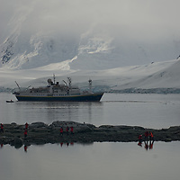 Tourists from the National Geographic Endeavor explore a cove at Damoy Point on Wiencke Island, Antarctica. Behind are mountains on Anvers Island.
