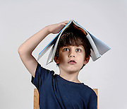 Mischievous and bored boy of 6 plays with a book