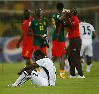 Photo: Steve Bond/Richard Lane Photography.<br />Ghana v Cameroon. Africa Cup of Nations. 07/02/2008. Hans Adu Sarpei (seated) is dejected as Cameroon players celebrate