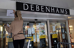 © Licensed to London News Pictures. 02/12/2020. Harrow, UK. A worker puts a temporary 'EXIT' sign at the entrance to a branch of Debenhams as it opens at 9am in Harrow, north London. Debenhams is set to close putting 12,000 jobs at risk. A tiered system of local lockdowns will now come into force in England with non-essential retail, gyms, hairdressers and other personal care businesses allowed to open after England's month long lockdown came to an end. Photo credit: Peter Macdiarmid/LNP