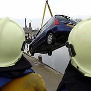 NLD/Huizen/200600203 - Auto te water, Havenstraat Huizen, takelbedrijf Dorresteijn takelt hem uit het water, brandweer, schade, total los, kade, wal, helmen,