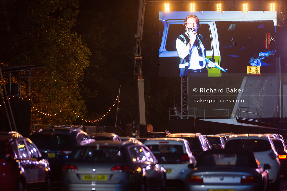 Rows of cars are parked in front of the stage to watch British Bass-baritone<br /> Paul Sheehan (playing Benoit) at the start of Puccini's La bohème, performed by members of  English National Opera (ENO) as a drive-in (ENO Drive and Live) at Alexandra Palace, on 18th September 2020, in London, England. This is ENO's first public performance since the closure of their West End Colisseum home venue, because of the Coronavirus pandemic lockdown in March. This is Europe's first live drive-in opera production that audiences can safely experience from their cars and ENO's first public performance since the closure of their West End Colisseum home venue, because of the Coronavirus pandemic lockdown in March. As per the latest government advice. Each bubbled group consists of; 34 members of the<br /> ENO Orchestra, 20 ENO Chorus members and 8 principals. Each bubble has its own individual crew to oversee their rehearsals and performances.