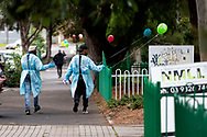 Medical personnel wearing full PPE are seen leaving the Sutton Street housing complex as balloons have been placed on the fence in support of the residents amid the third full day of the total lockdown of 9 housing commission high rise towers in North Melbourne and Flemington during COVID 19.After recording 191 COVID-19 cases overnight forcing Premier Daniel Andrews to announce today that all of metropolitan Melbourne along with one regional centre, Mitchell Shire will once more go back to stage three lockdowns from midnight Wednesday June 8. This comes as the residents of the housing commission towers in North Melbourne and Flemington finish their third day under extreme lockdown, despite only 27 cases being found in the towers. Members of the public gathered outside of the towers this afternoon in support of those trapped inside while riot police arrested two women for standing too close to the fence. While the women were later released, tensions are boiling over both in the towers and out. With 772 active cases in Victoria, NSW closed their border to Victoria effective at midnight tonight.