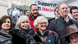 "© Licensed to London News Pictures. 23/11/2015. LONDON, UK. Actor, Bertie Carvel, former Doctor Who, Peter Davison, former Doctor Who girls, Sophie Aldred and Katy Manning, and June Hudson (inventor of Doctor Who's iconic long scarf) stand with fans of Doctor Who known as ""Whovians"" and other supporters of the BBC as they gather outside Broadcasting House in central London to oppose the threat of 20% government cuts to the Corporation which has brought shows such as Dr Who since 1922. Photo credit : Stephen Chung/LNP"