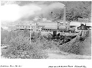 """American Smelter Works on west side of Animas River at Durango as seen from the D&RGW yard.  Notice the footbridge at lower left.<br /> Durango, CO  ca. 1901<br /> Print from original Albumen photo.<br /> Dorman's """"Durango"""" has a similar, but different, photo on p. 12."""