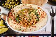 Hummus. A Levantine Arab dip or spread made from cooked, mashed chickpeas, blended with tahini, olive oil, lemon juice, salt and garlic. Garnished with cooked chickpeas