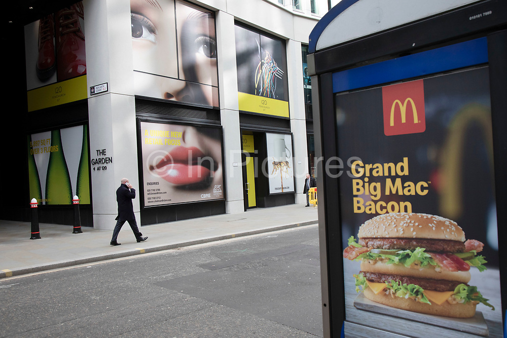 Giant advertising face with full lips and eyes looking down onto a McDonalds advert and people passing below on Fenchurch Street in the City of London, United Kingdom. The atmosphere is one of being watched and of Big Brother watching you.
