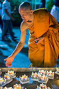 28 NOVEMBER 2012 - BANGKOK, THAILAND: A Buddhist monk cleans a pool of krathongs on Loy Krathong at Wat Yannawa in Bangkok. Loy Krathong takes place on the evening of the full moon of the 12th month in the traditional Thai lunar calendar. In the western calendar this usually falls in November. Loy means 'to float', while krathong refers to the usually lotus-shaped container which floats on the water. Traditional krathongs are made of the layers of the trunk of a banana tree or a spider lily plant. Now, many people use krathongs of baked bread which disintegrate in the water and feed the fish. A krathong is decorated with elaborately folded banana leaves, incense sticks, and a candle. A small coin is sometimes included as an offering to the river spirits. On the night of the full moon, Thais launch their krathong on a river, canal or a pond, making a wish as they do so.    PHOTO BY JACK KURTZ
