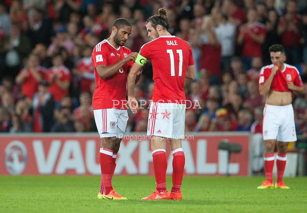 CARDIFF, WALES - Monday, September 5, 2016: Wales Ashley Williams hands over the captains arm band to Gareth Bale in action against Moldova during the 2018 FIFA World Cup Qualifying Group D match at the Cardiff City Stadium. (Pic by Ian Cook/Propaganda)