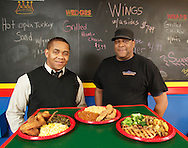 Owner Seneca King, left, and chef Willie Martin pose for a portrait with three dishes at Kings Korner Deli on East Main Street in M iddletown on Monday, Jan. 17, 2011. The dishes are: fried chicken wings with collard greens and mac and cheese; fried fish with red beans and yellow rice; and grilled pork chops with roasted potatoes and broccoli.