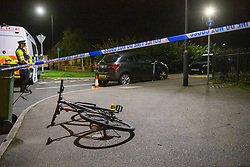 © Licensed to London News Pictures. 15/08/2021. Slough, UK. A police officer guards a scene marked out with police tape surrounding a bike and evidence markers following a double stabbing in Cippenham, Slough. Emergency services were called at approximately 17:00BST on Sunday 15/08/2021 to the Eltham Avenue area of Slough to reports that two male teenagers had been assaulted during an altercation between a number of youths. Both were taken to hospital with stab wounds. Photo credit: Peter Manning/LNP
