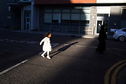 Child walks through a shaft of evening light, casting a shadow of herself in East London, UK. On her way to a social event with her mother, she is struggling to walk in her heels, which match her white party dress.