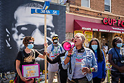 """15 AUGUST 2020 - MINNEAPOLIS, MINNESOTA:  Women rally in front of a large portrait of George Floyd in front of Cup Foods at the George Floyd Memorial in Minneapolis. Floyd, an unarmed Black man, was killed by Minneapolis police officers of May 25 in front of Cup Foods, a convenience store at the intersection of 38th and Chicago Ave. His killing sparked a week of violent protests across the country. The intersection where he was killed is still closed and has become an unofficial memorial visited by hundreds of people every day. Saturday, more than 100 people gathered at the memorial to demand the city preserve the memorial. On Saturdays in August, the intersection has a market, with venders selling Afro-centric merchandise. The city of Minneapolis had planned to start reopening the intersection as soon as Monday Aug. 17, but delayed those plans indefinitely on Friday, Aug. 14. City residents have created a """"George Floyd Zone"""" at the intersection. They're demanding the recall of Hennepin County Attorney Mike Freeman, requiring Minneapolis police officers have their own private liability insurance, and the allocation of funds for businesses and residents in the community. The city is considering officially renaming Chicago Ave. between 37th and 39th """"George Floyd Jr. Place.""""    PHOTO BY JACK KURTZ"""