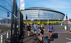 Glasgow, Scotland, UK. 21st October 2021. Final preparations underway at the site of the UN Climate Change Conference COP26 to be held in Glasgow from Oct 31st. Pic; Joggers run around the perimeter of the COP26 site.  Iain Masterton/Alamy Live News.