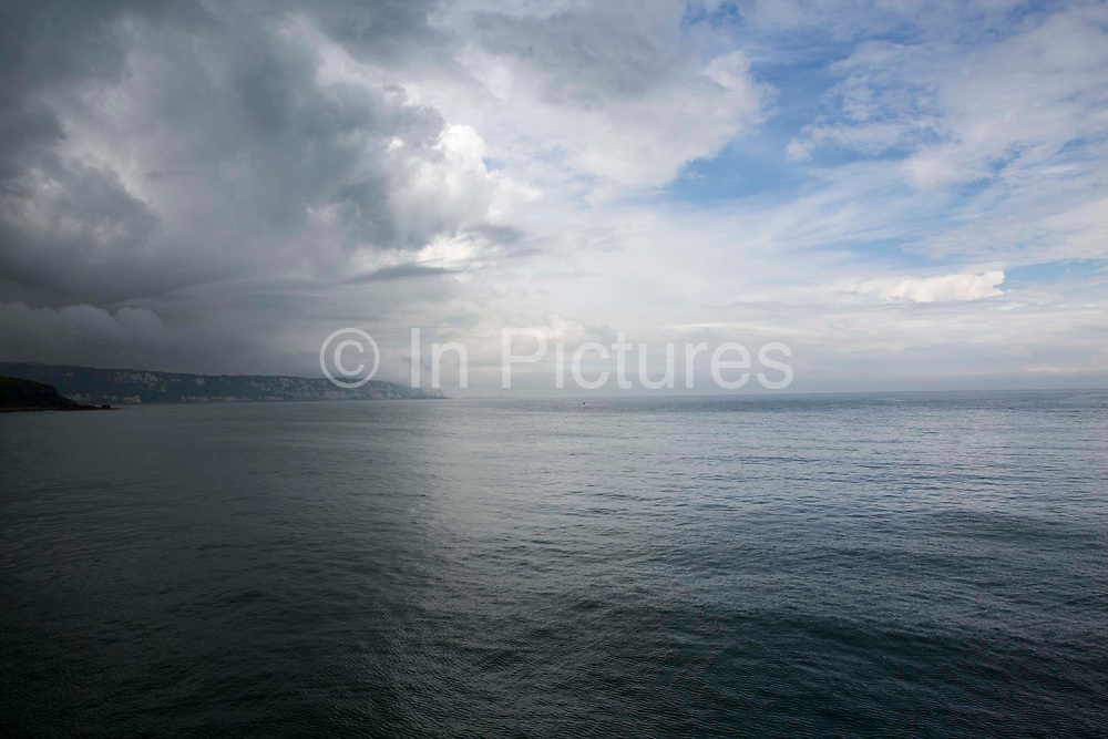 Dramatic dark and white clouds in the sky above The White Cliffs of Dover and the Strait of Dover of The English Channel, photographed from Folkestone Kent, England, United Kingdom.