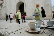 People stroll past empty coffee cups and saucers.<br /> Trogir, Croatia