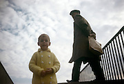 A young boy of about 5 years-old stands on a seaside bridge as an older man walks past in the early 1960s. Seen from a low angle, we look up at the small boy standing on some steps of a bridge on the seafront at Southend-on-Sea in Essex, recorded on a film camera by the boy's father, an amateur photographer in 1962. The picture shows us a memory of nostalgia in an era from the last century.