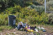 Trash can and trash in Ballona Wetlands, Playa Vista, Los Angeles, California, USA