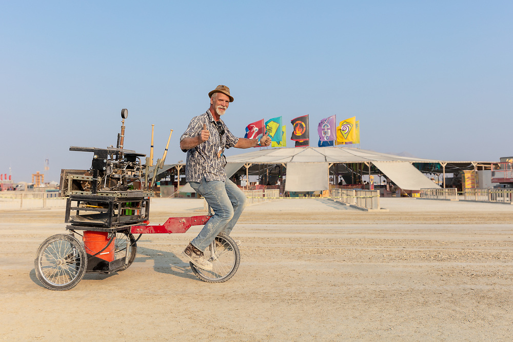 Shots Fired Espresso Cart by: PocoJoe and the Shots Fired Team from: Tucson, AZ year: 2018 (This fellow said can you take a photo of me so I can send it to my wife. She didn't think it was possible to put an espresso machine on a unicycle.) My Burning Man 2018 Photos:<br /> https://Duncan.co/Burning-Man-2018<br /> <br /> My Burning Man 2017 Photos:<br /> https://Duncan.co/Burning-Man-2017<br /> <br /> My Burning Man 2016 Photos:<br /> https://Duncan.co/Burning-Man-2016<br /> <br /> My Burning Man 2015 Photos:<br /> https://Duncan.co/Burning-Man-2015<br /> <br /> My Burning Man 2014 Photos:<br /> https://Duncan.co/Burning-Man-2014<br /> <br /> My Burning Man 2013 Photos:<br /> https://Duncan.co/Burning-Man-2013<br /> <br /> My Burning Man 2012 Photos:<br /> https://Duncan.co/Burning-Man-2012